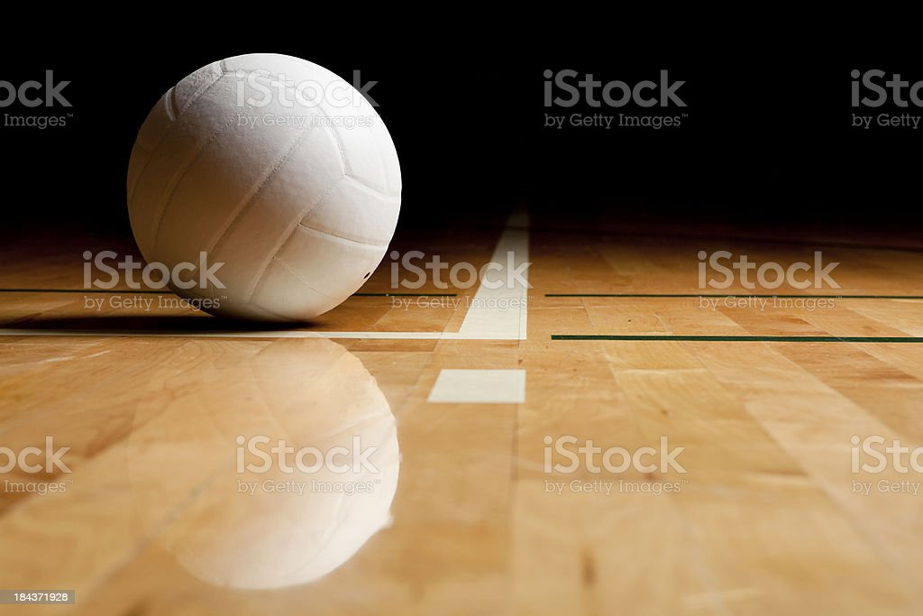 A volleyball and reflection on a wooden floor stock photo