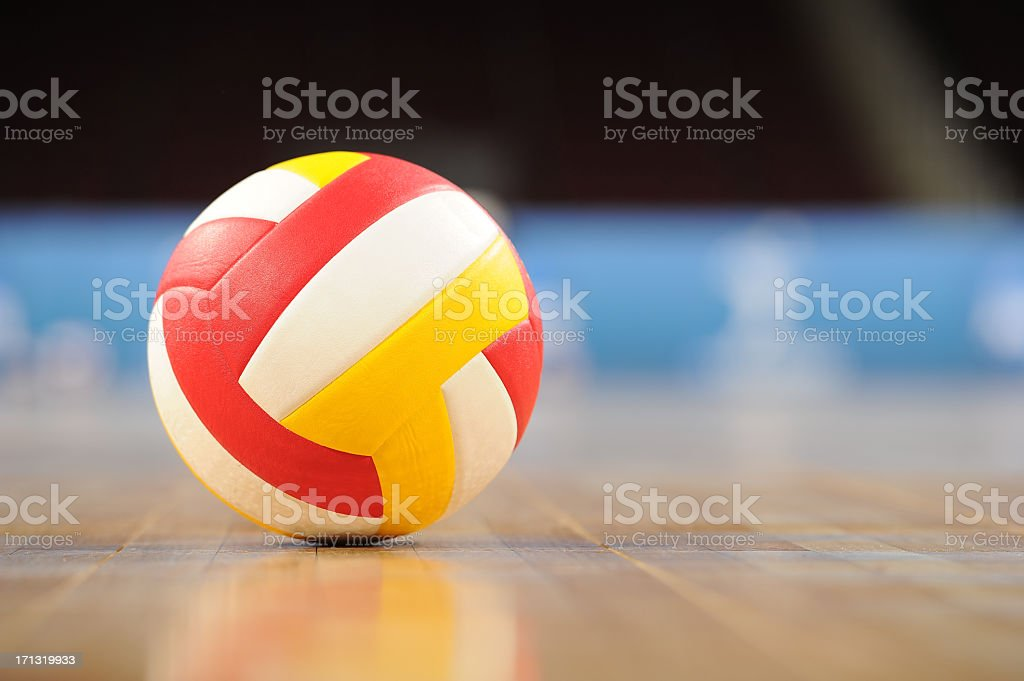 A volleyball on a wooden gym floor stock photo