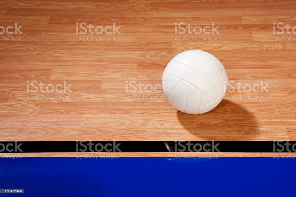 Volleyball on Hardwood Court stock photo