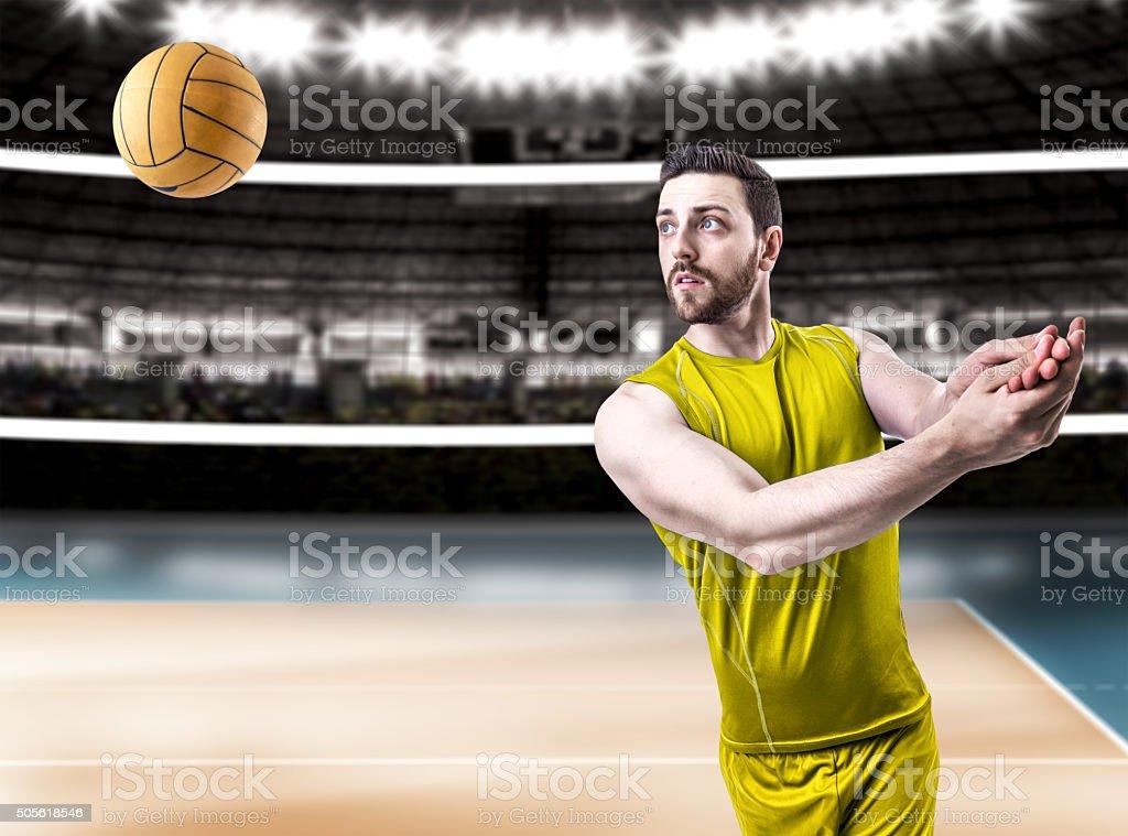 Volleyball player on yellow uniform on the stadium stock photo