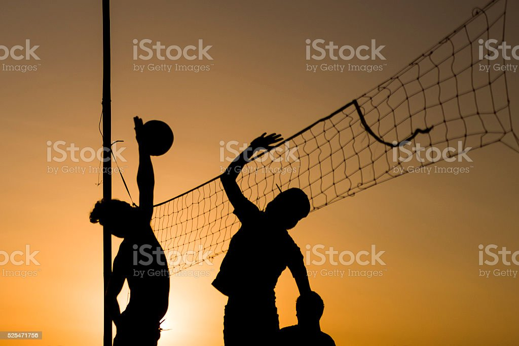 Volleyball playing people silhouettes stock photo