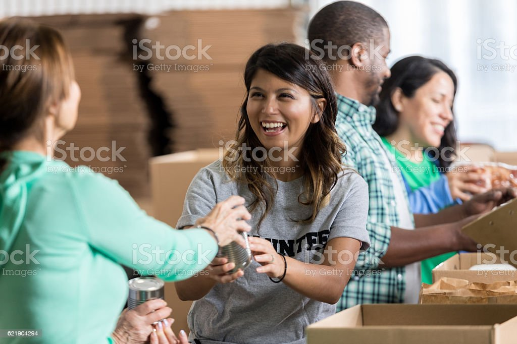 Volunteer accepts canned food donation at food drive stock photo