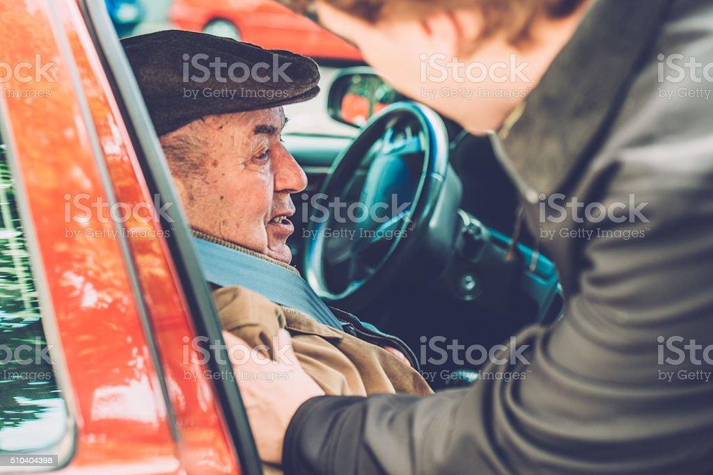 Volunteer, Assistant, Grandson Helping Senior Man into the Car, Europe stock photo