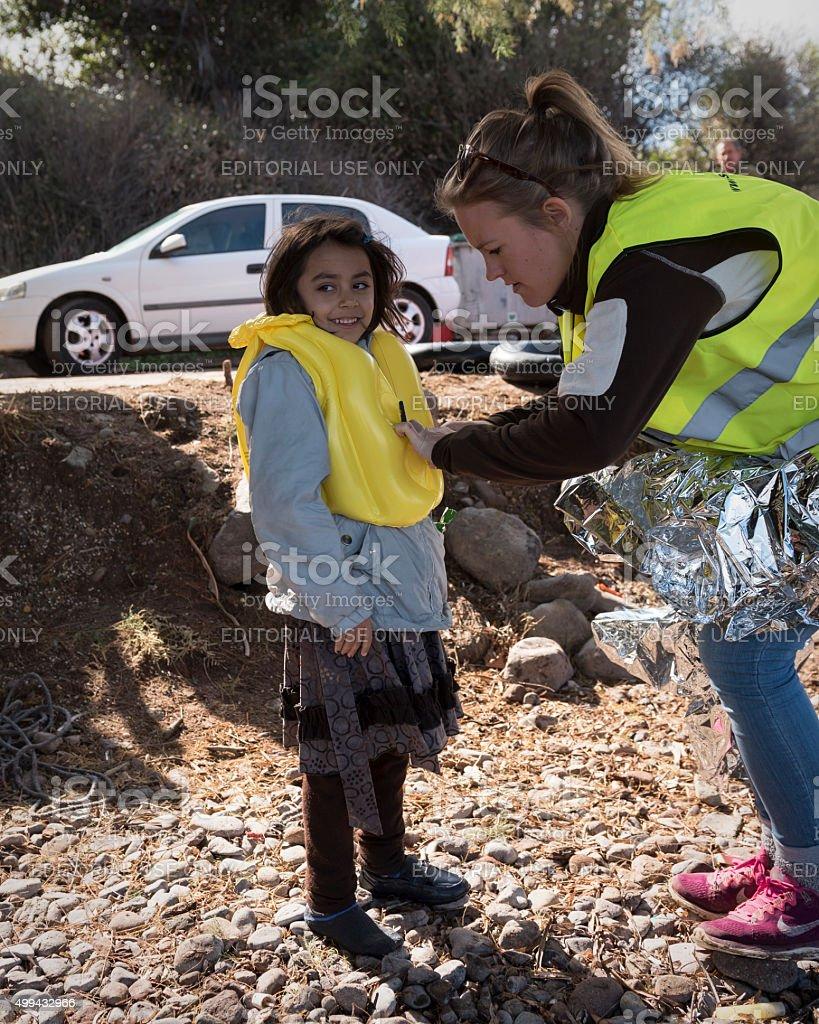 volunteer assisting refugee girl on Lesbos, Greece stock photo