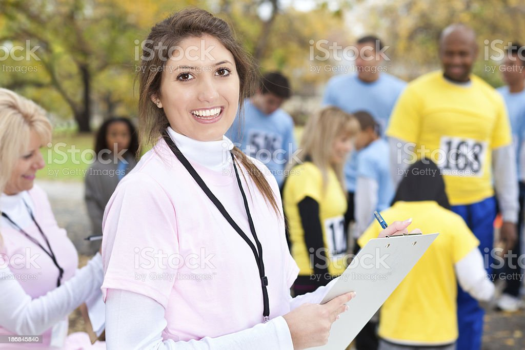 Volunteer checking people in for a charity event race royalty-free stock photo