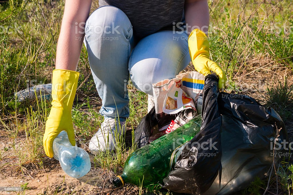 Volunteer girl in yellow gloves collects garbage selective focus stock photo