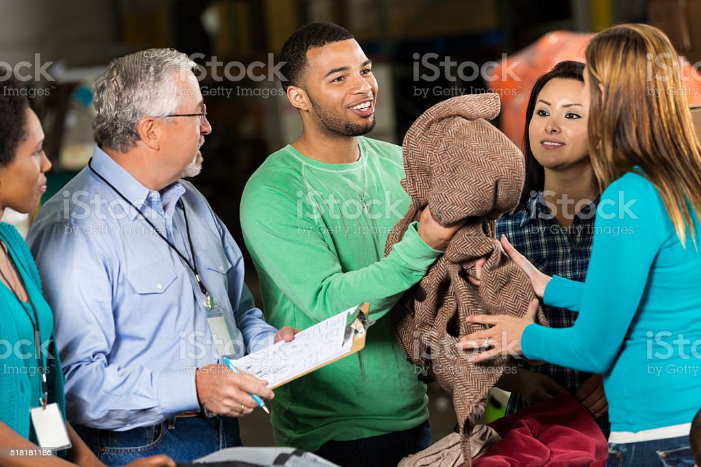 Volunteer hands out coats at clothing drive stock photo