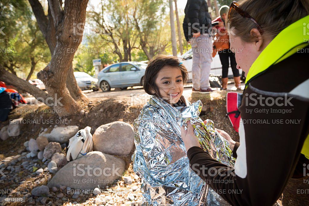 Volunteer helping refugee girl on beach stock photo