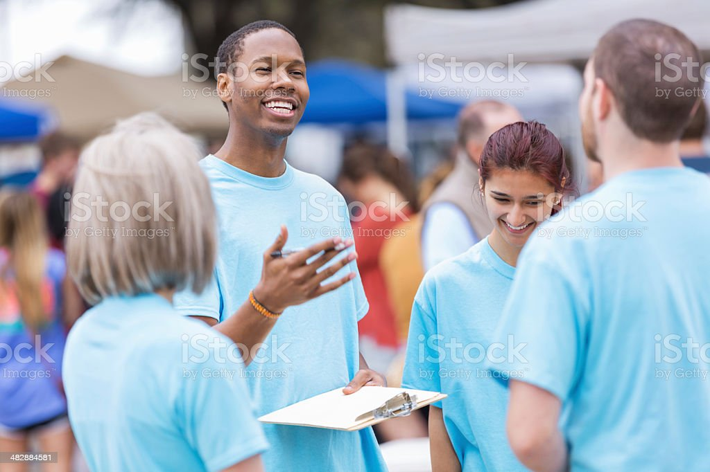 Volunteer leader giving instructions at outdoor festival or market stock photo