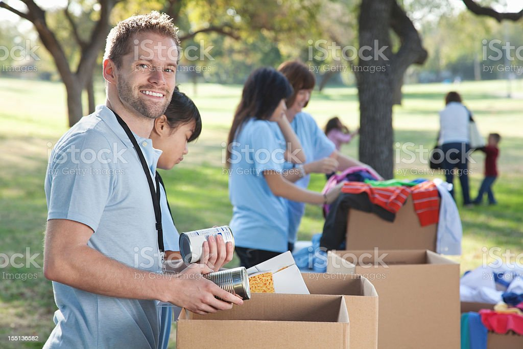Volunteer looking back while sorting through donations stock photo