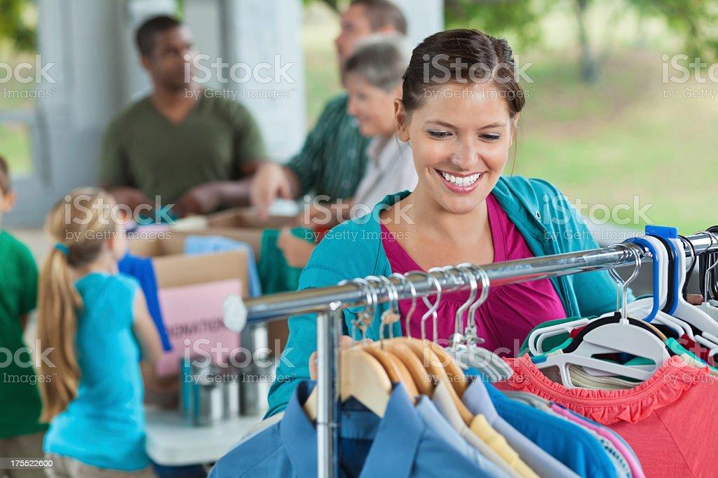 Volunteer organizing racks of clothing at charity donation drive stock photo