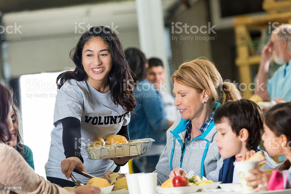 Volunteer serves meal to homeless in shelter stock photo
