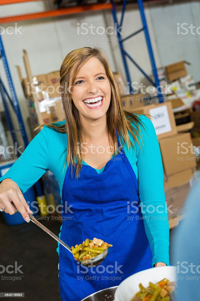 Volunteer serving hot meal to people at soup kitchen royalty-free stock photo
