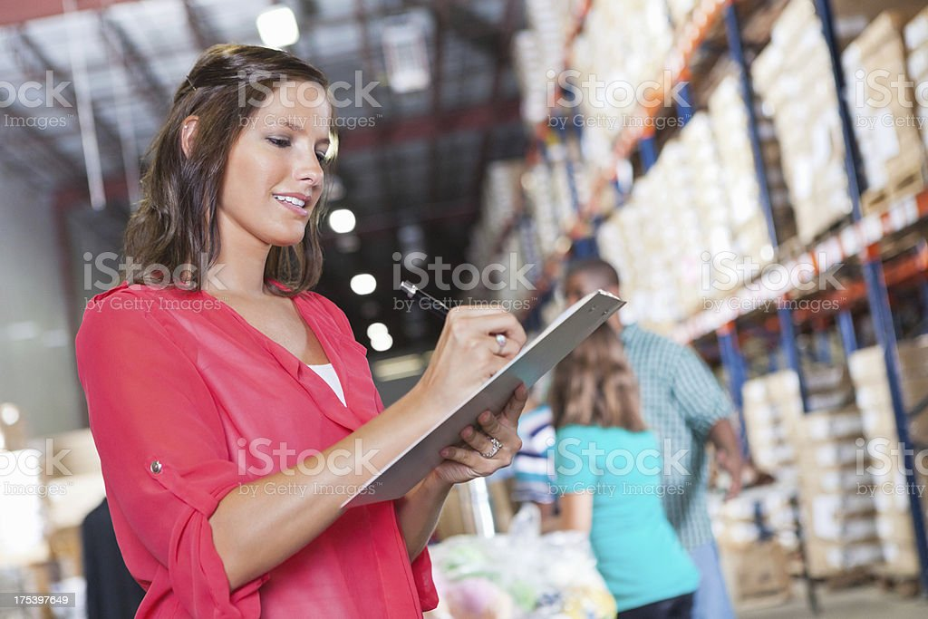 Volunteer taking inventory of food donations from drive at warehouse royalty-free stock photo