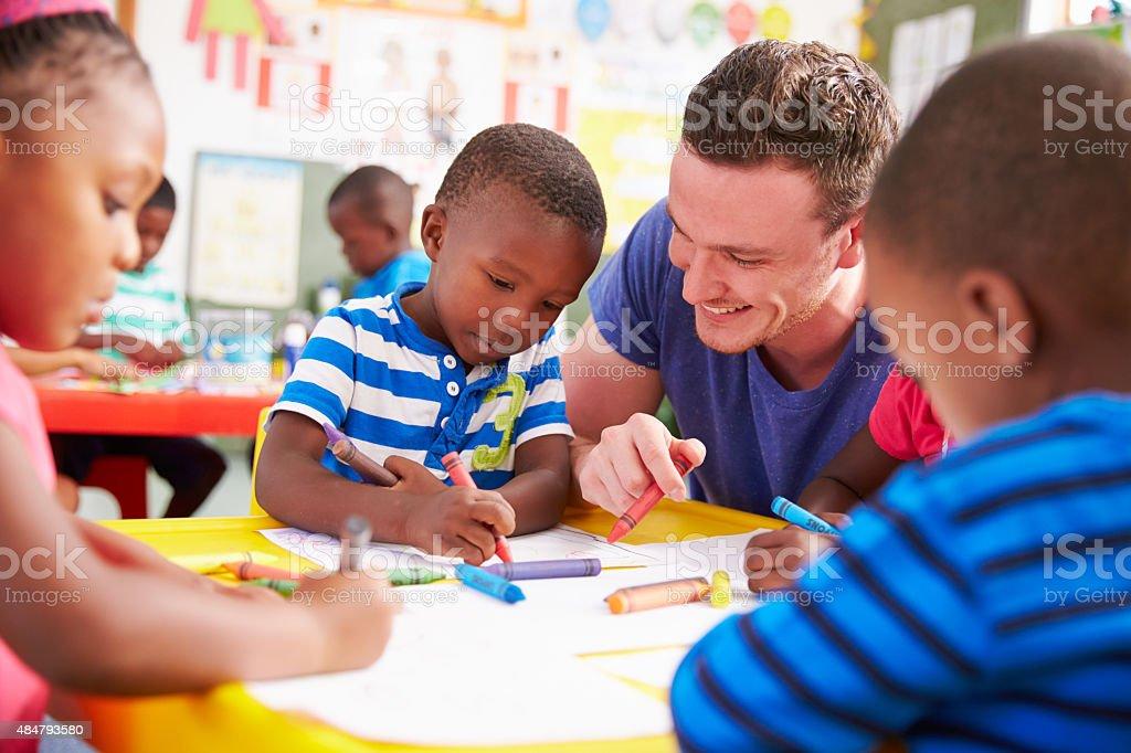 Volunteer teacher helping a class of preschool kids drawing stock photo