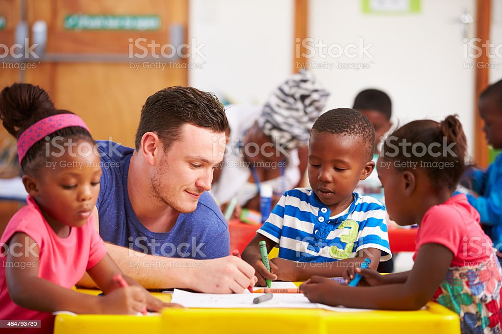 Volunteer teacher sitting with preschool kids in a classroom stock photo