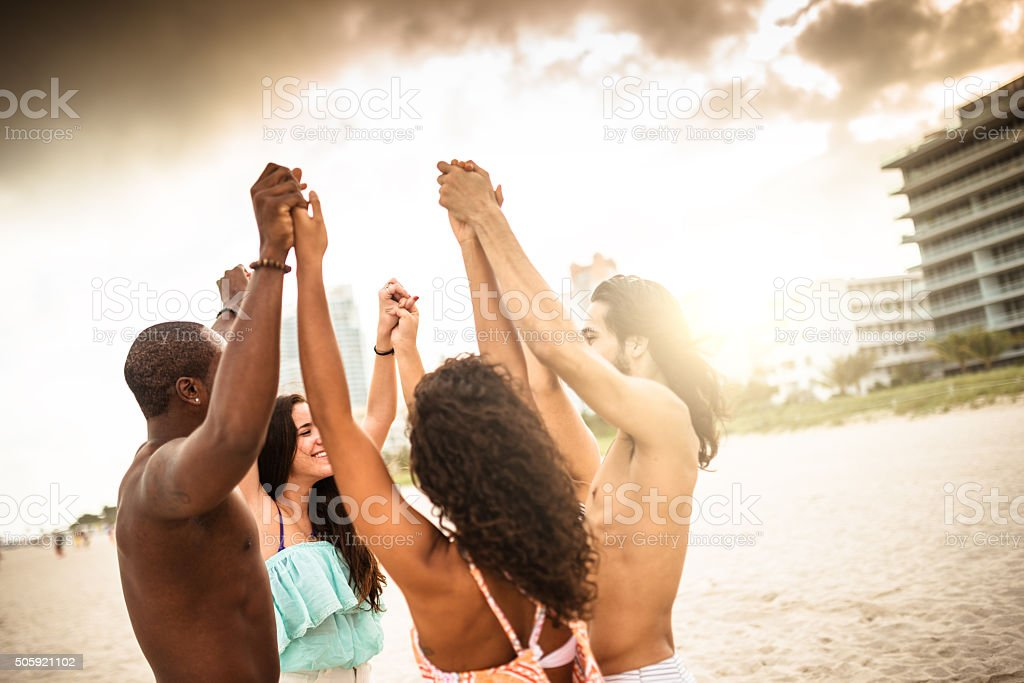 volunteer togetherness at dusk on the beach stock photo