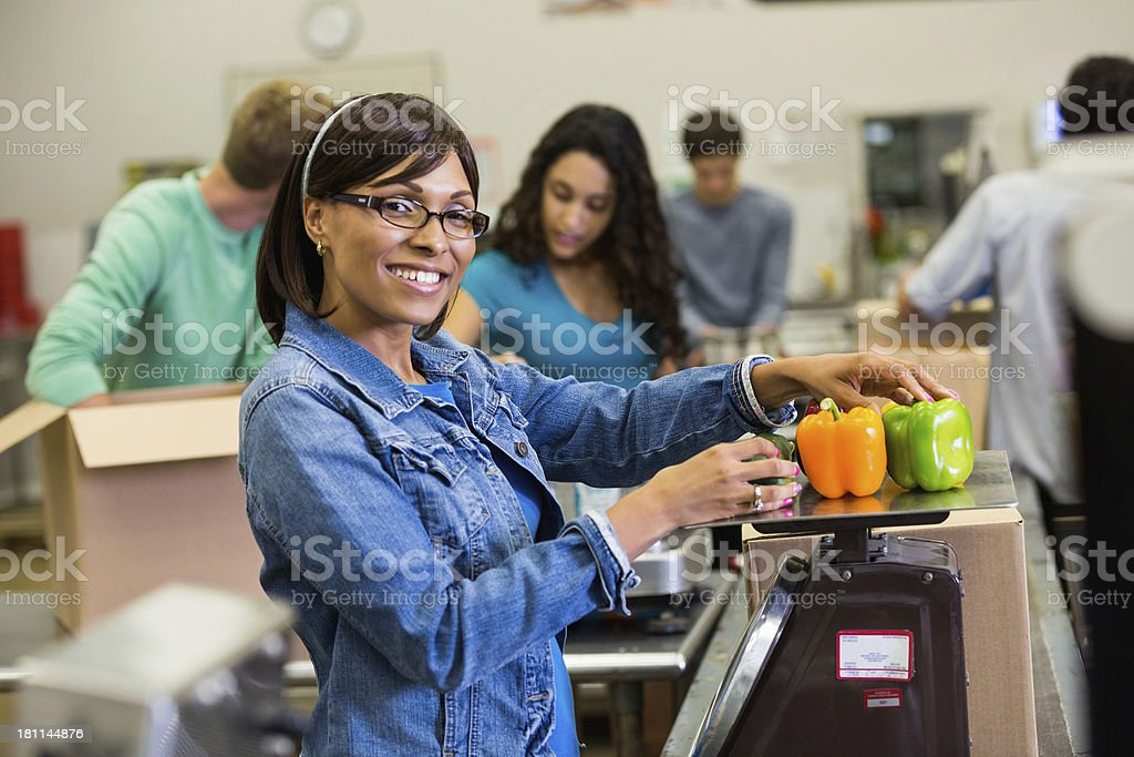 Volunteer weighing and sorting healthy food donations royalty-free stock photo