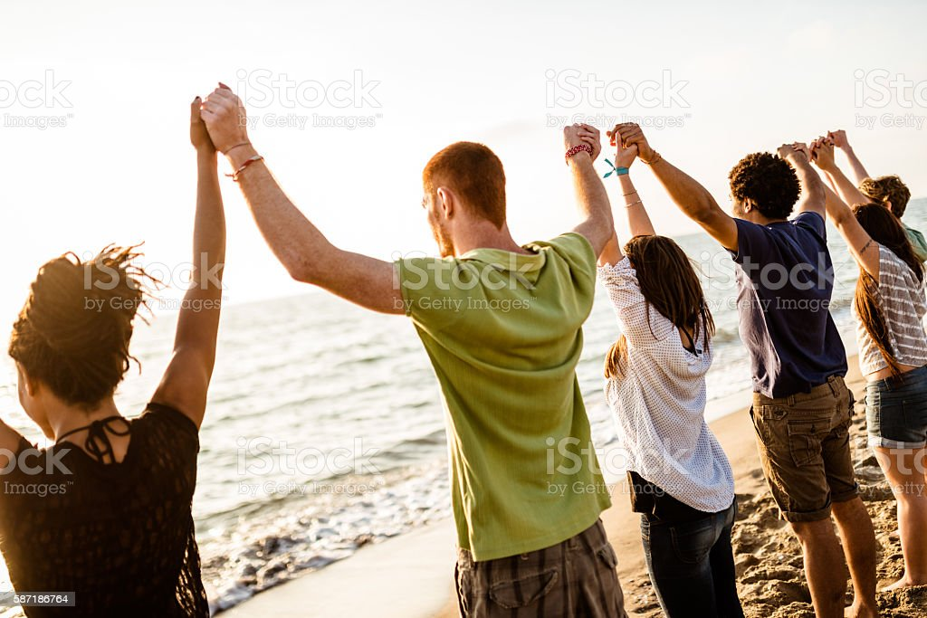 volunteer with arm raised at sunset stock photo