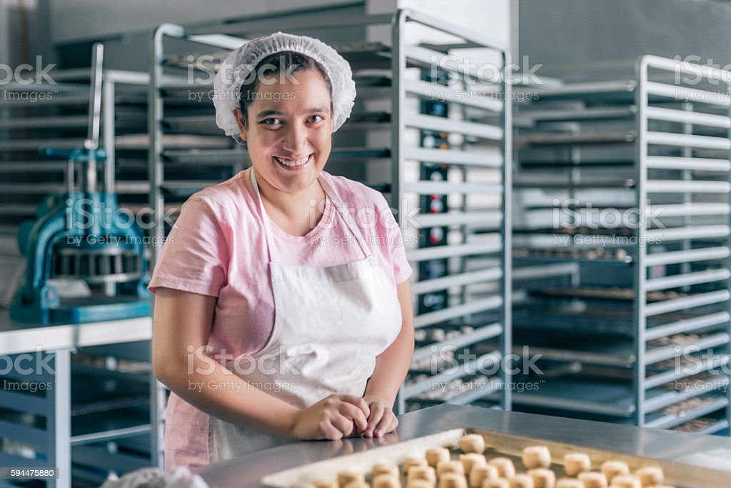Volunteer with intelectual disability working at Bakery Workshop stock photo