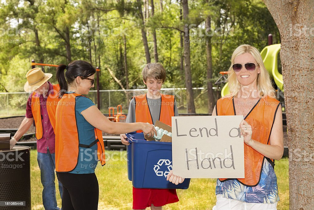 Volunteerism:  Mixed age people picking up trash in a park. royalty-free stock photo