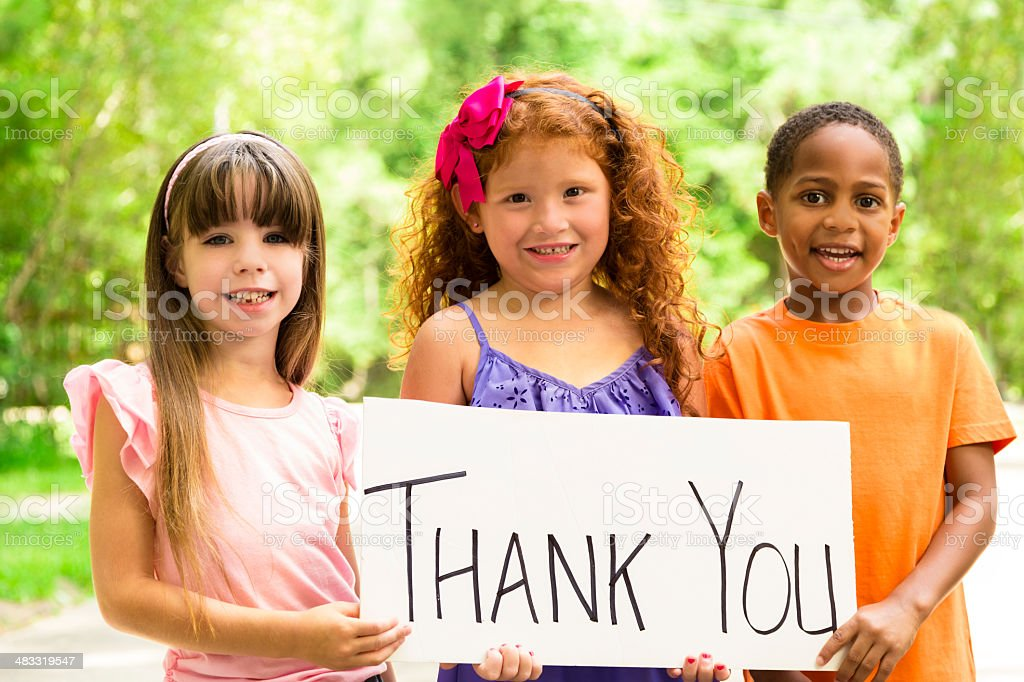 Volunteerism:  Three precious children holding a Thank You sign. Charity. stock photo