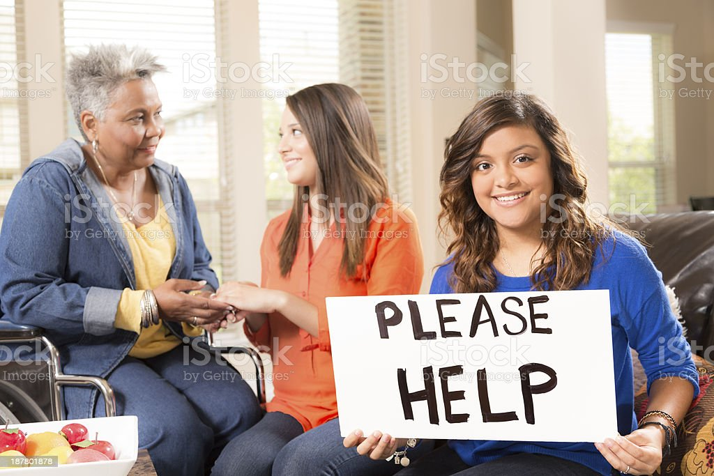 Volunteerism:  Young adults visit senior woman in nursing home. stock photo