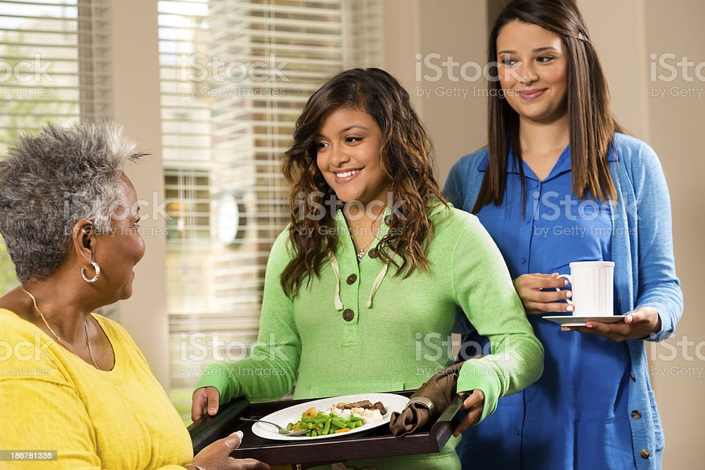 Volunteerism: Young people provide meal to senior woman. royalty-free stock photo