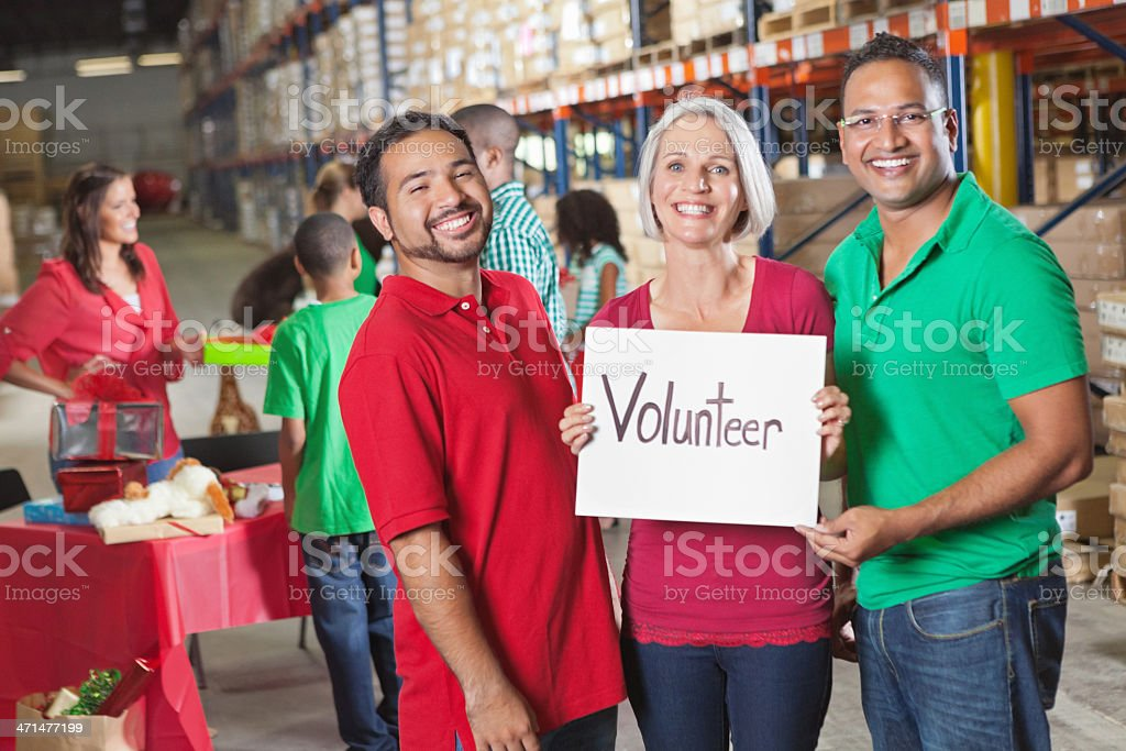Volunteers at charity toy food donation drive, 'volunteer' sign royalty-free stock photo