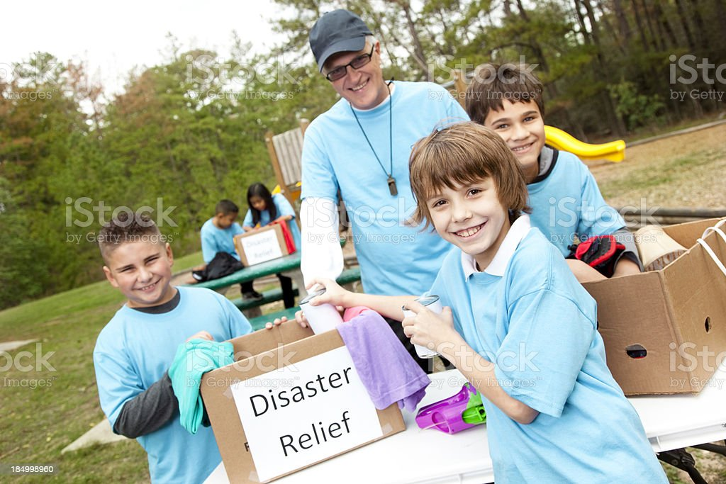 Volunteers: Children sports team collects donations for disaster relief aid. stock photo