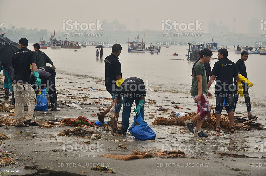 Volunteers cleaning up beach during Ganesha festival royalty-free stock photo