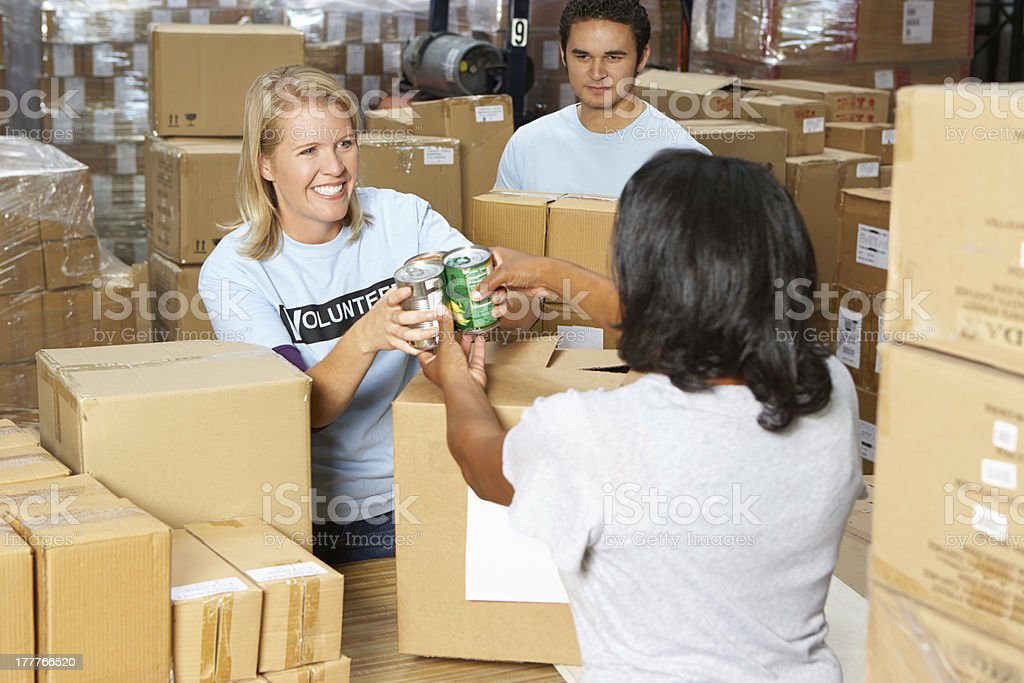 Volunteers collecting food donations in a warehouse stock photo