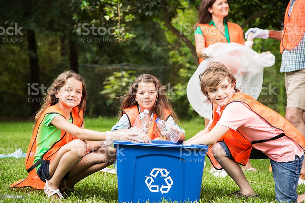 Volunteers: Family cleans up their community park. Recycling bin. stock photo