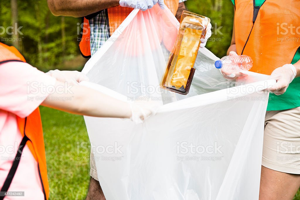Volunteers: Family cleans up their community park. Teamwork. stock photo