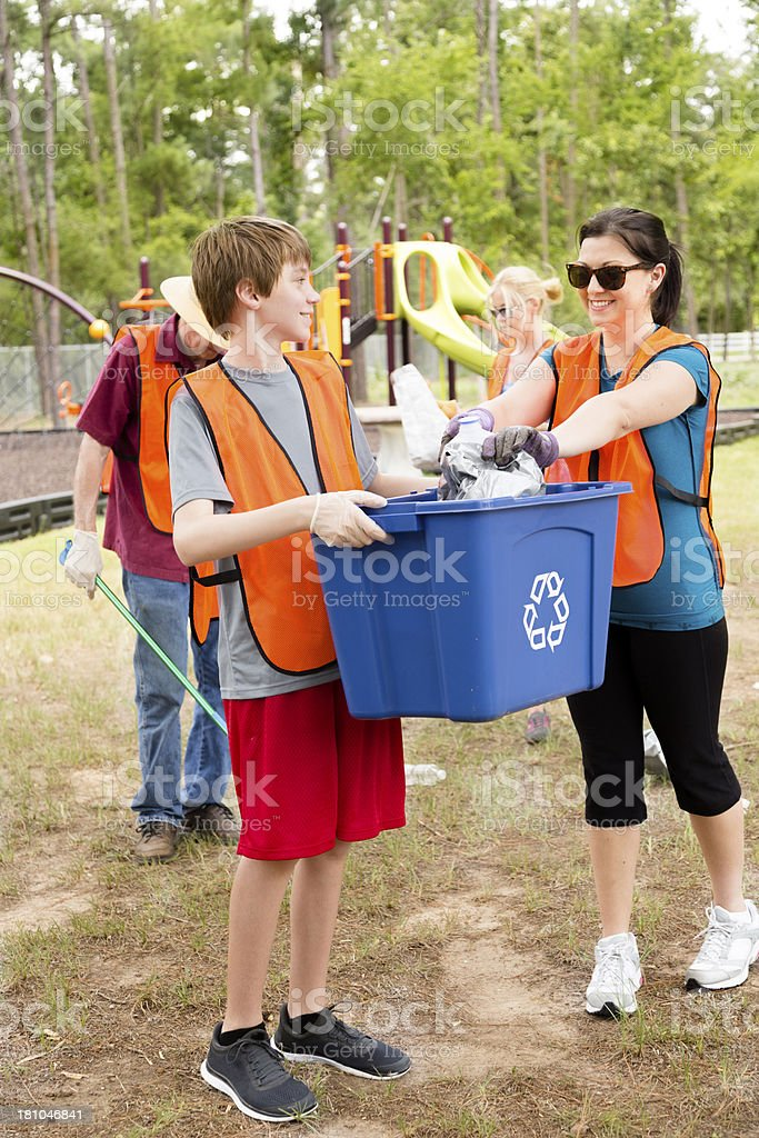 Volunteers:  Family picking up trash in a park. Recycle bin. royalty-free stock photo