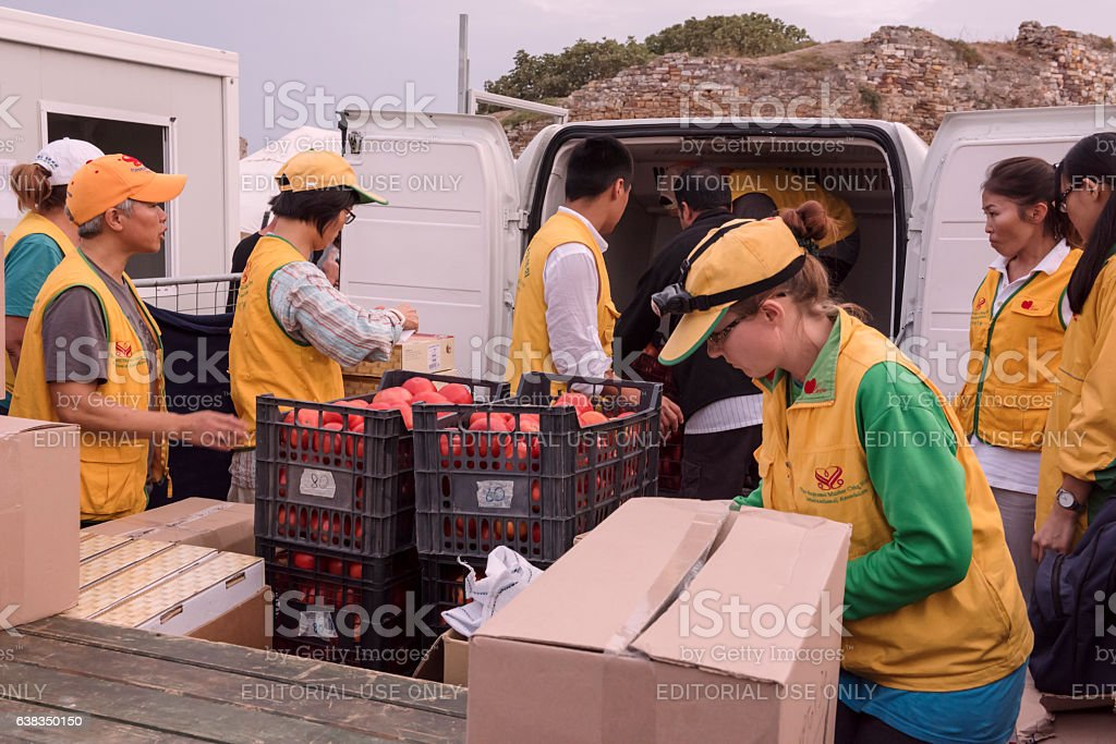 Volunteers getting ready to serve dinner in Greek refugee camp stock photo