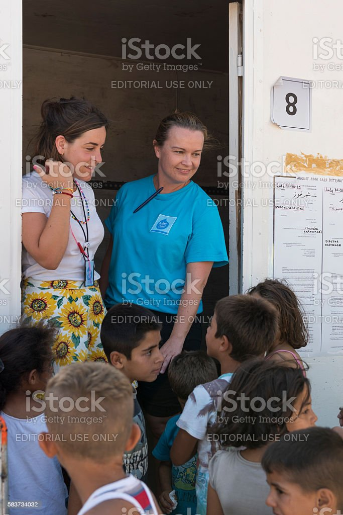 Volunteers greet refugee children at a improvised classroom on Chios stock photo