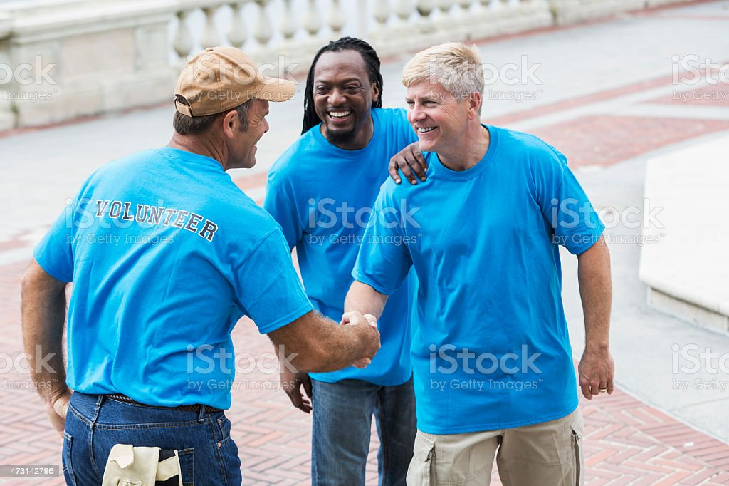 Volunteers meeting at a park shaking hands stock photo