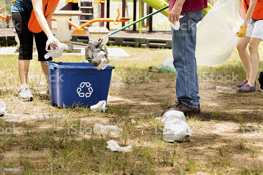 Volunteers: Mixed-age people pick up trash in park. Recycle bin. stock photo
