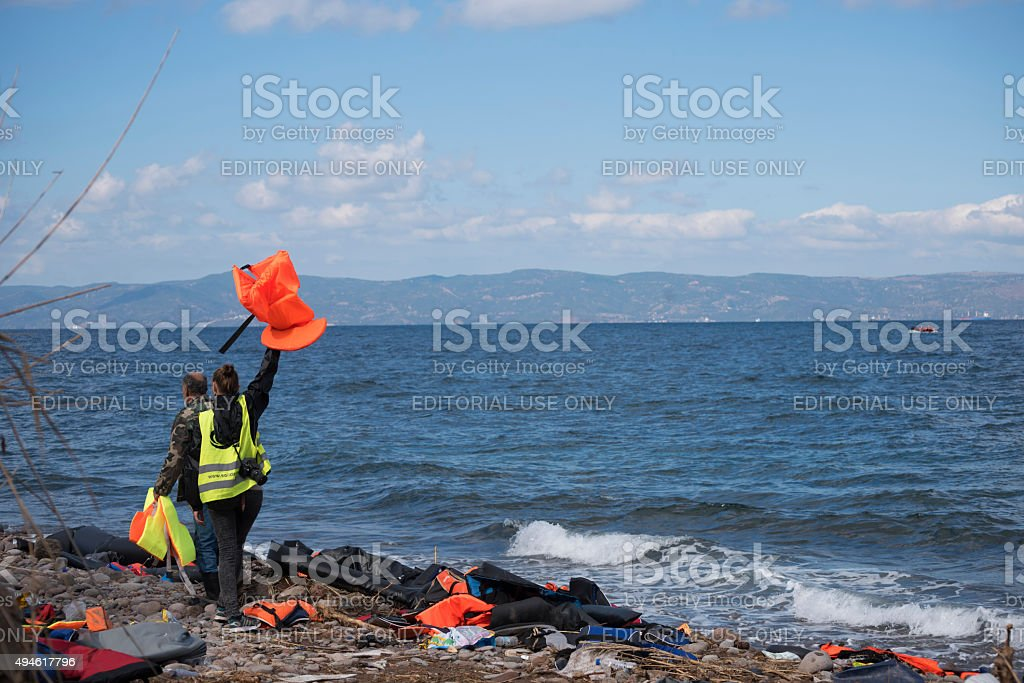 Volunteers on Lesbos signal to approaching refugee boat stock photo