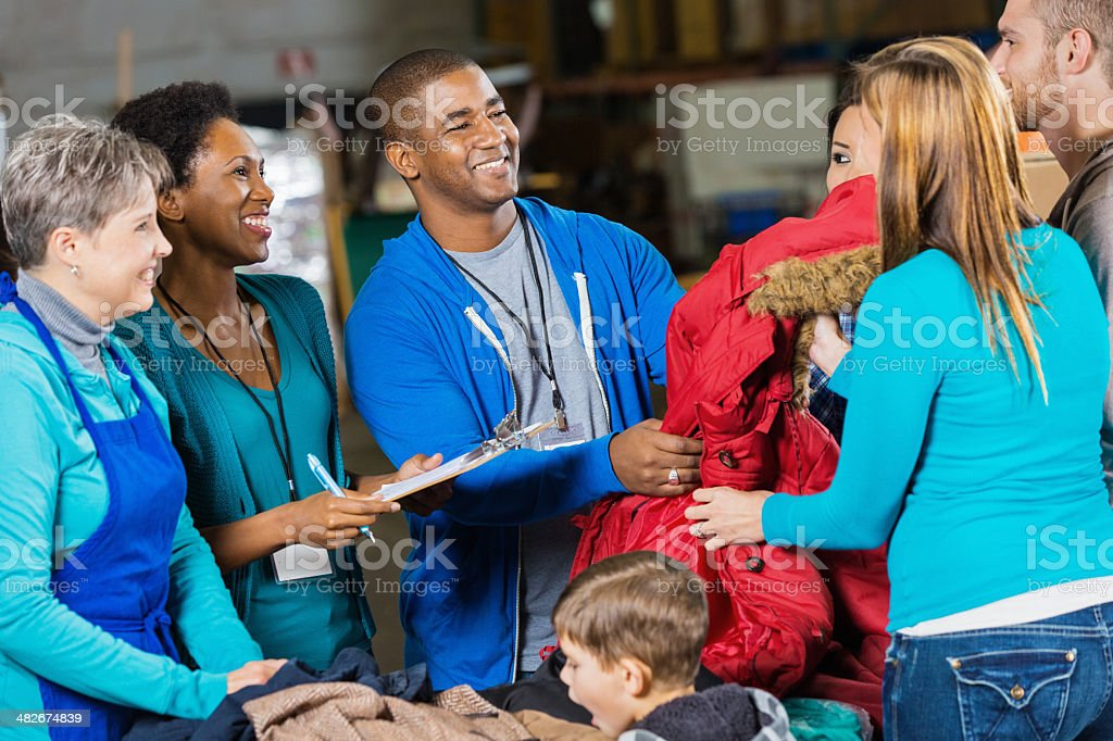 Volunteers passing out coats at winter clothing donation drive stock photo