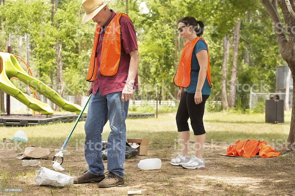 Volunteers:  People picking up trash in a park.  Playground. royalty-free stock photo