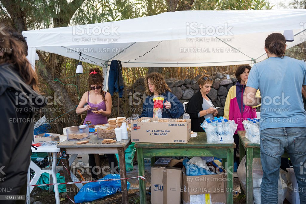 Volunteers providing food and drink to refugees on Lesbos stock photo