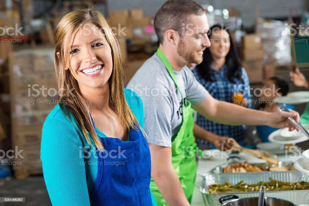 Volunteers serves food at soup kitchen stock photo