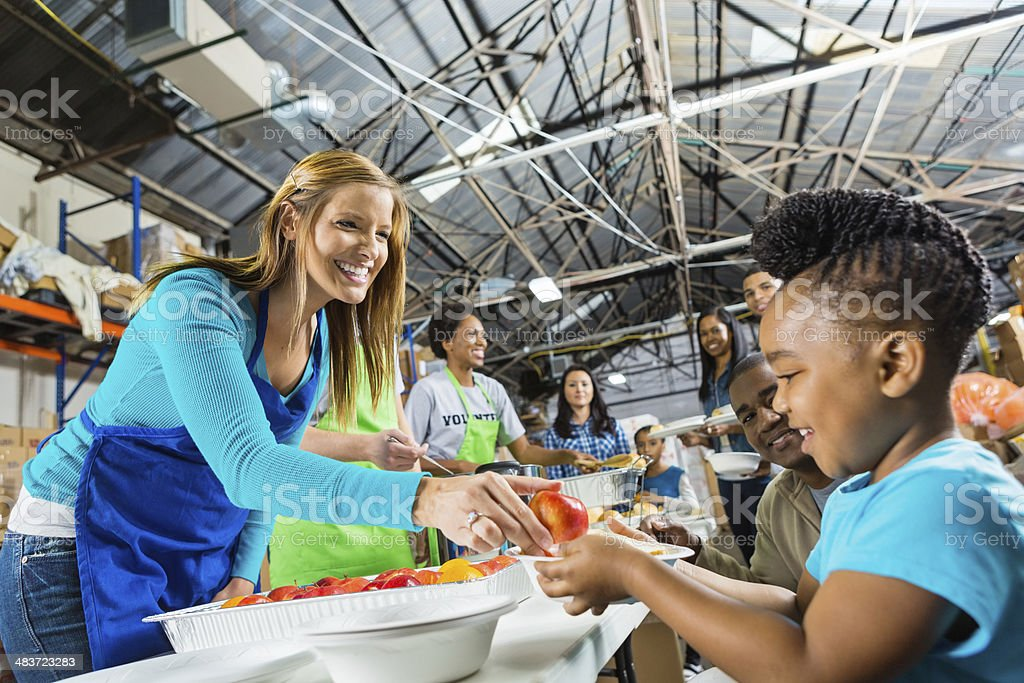 Volunteers serving healthy hot meal at food bank soup kitchen stock photo