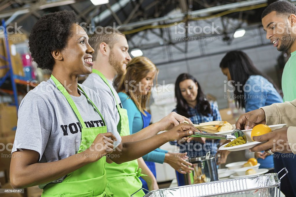 Volunteers serving healthy hot meal at soup kitchen stock photo