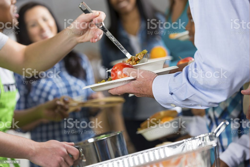 Volunteers serving hot meal to people at community soup kitchen stock photo