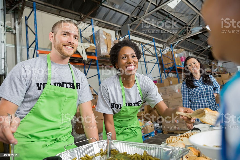 Volunteers serving hot meal to people in community soup kitchen stock photo