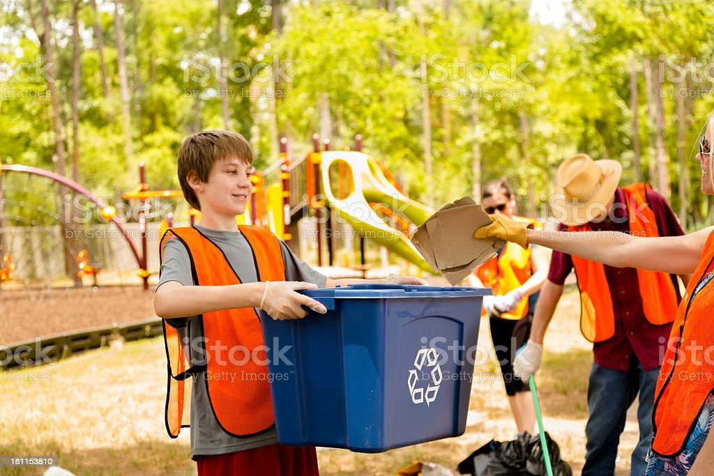 Volunteers: Teenage boy carries bin for fellow recyclers. Environmental Conservation stock photo