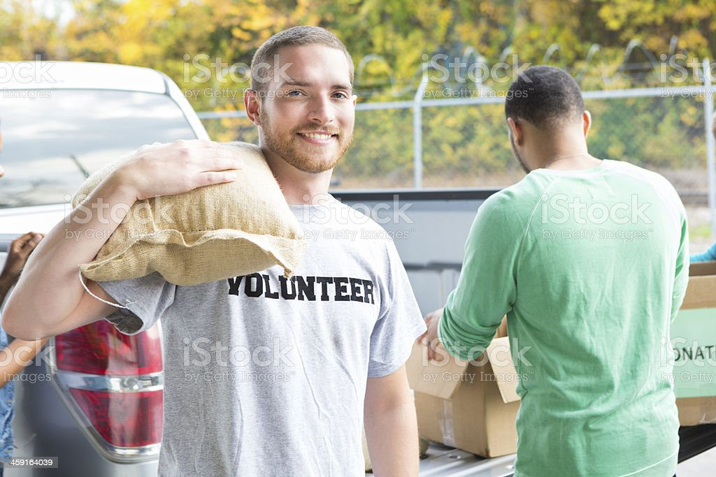 Volunteers unloading donated food from truck outside warehouse stock photo